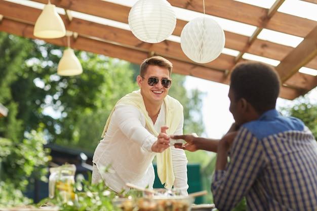 Retrato de jovem sorridente usando óculos escuros, passando o molho para um amigo na mesa enquanto desfruta de um jantar ao ar livre na festa de verão