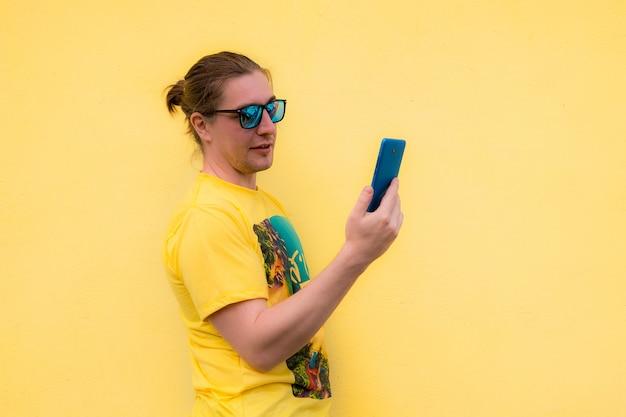 Retrato de jovem sorridente usando seu telefone celular
