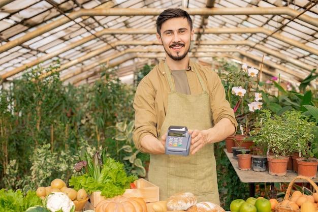 Retrato de jovem sorridente vendedor de supermercado com avental usando o terminal de pagamento no mercado do agricultor