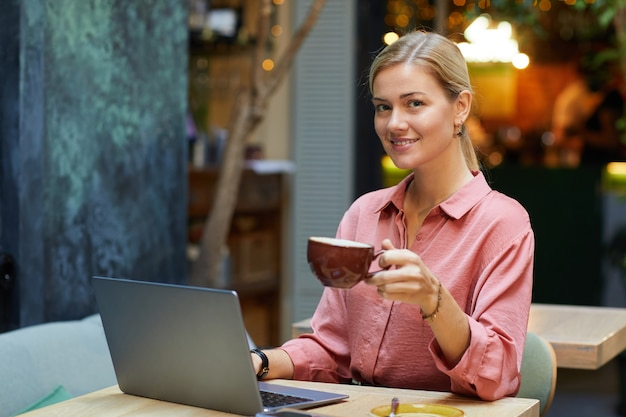 Retrato de jovem sorrindo e bebendo café enquanto trabalhava no laptop no café