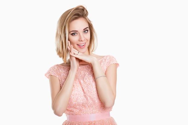 Retrato de jovem sorrindo linda loira sensual em um vestido rosa de coquetel em fundo cinza