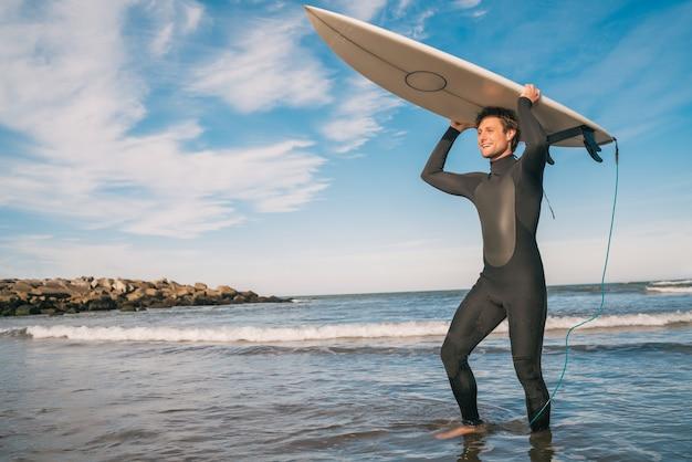 Retrato de jovem surfista na praia segurando sua prancha de surf e vestindo uma roupa de surf preta