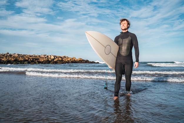 Retrato de jovem surfista saindo da água com a prancha debaixo do braço