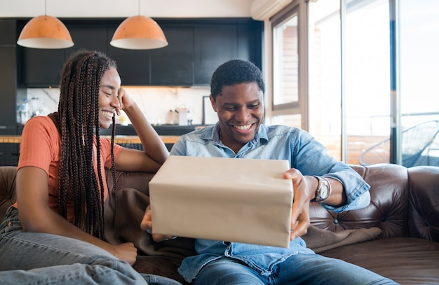 Retrato de jovem surpreendendo o namorado com uma caixa de presente.