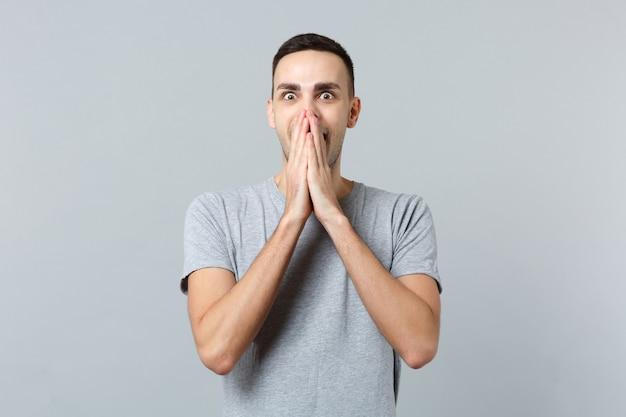 Retrato de jovem surpreso e chocado com roupas casuais, cobrindo a boca com as mãos