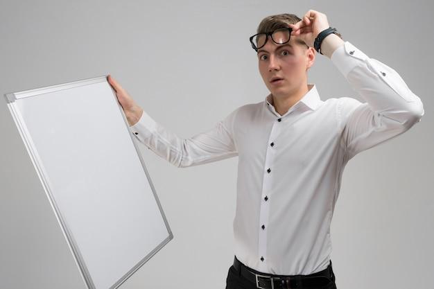 Retrato de jovem surpreso usando óculos com placa magnética limpa isolada