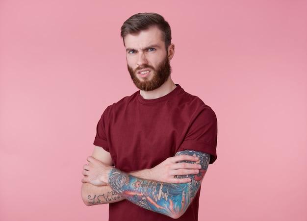 Retrato de jovem tatuado nojento homem barbudo vermelho em t-shirt em branco, fica com os braços cruzados sobre fundo rosa, carrancudo e olha para a câmera.