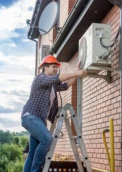 Retrato de jovem técnico consertando aparelho de ar condicionado externo
