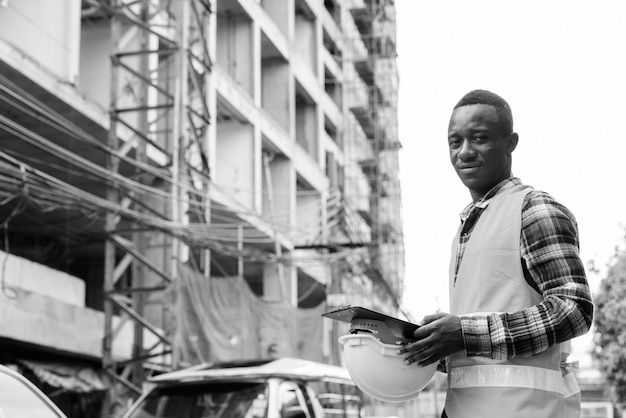 Retrato de jovem trabalhador da construção civil africano no canteiro de obras ao ar livre em preto e branco