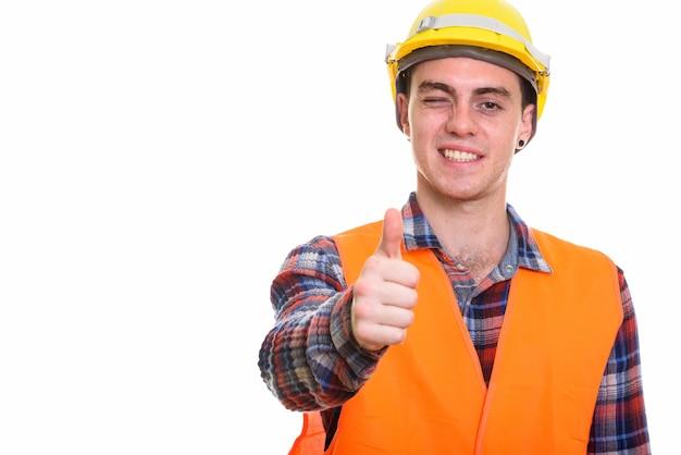 Retrato de jovem trabalhador da construção civil fazendo sinal de positivo