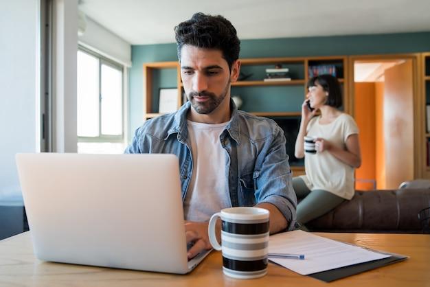 Retrato de jovem trabalhando com um laptop em casa enquanto uma mulher falando ao telefone no fundo