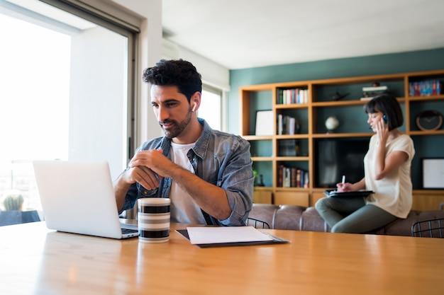 Retrato de jovem trabalhando com um laptop em casa enquanto uma mulher falando ao telefone