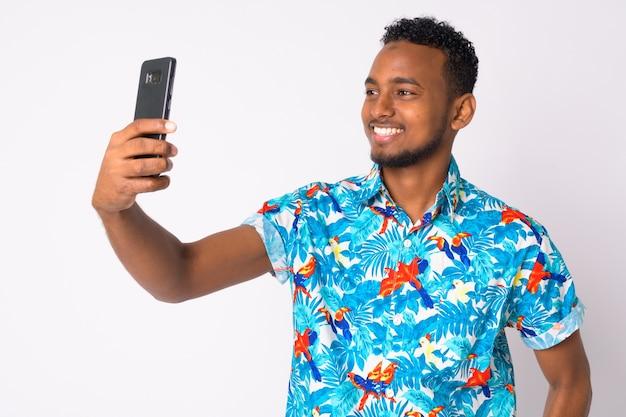 Retrato de jovem turista africano bonito contra uma parede branca