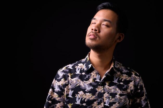 Retrato de jovem turista asiático com camisa boêmia em preto