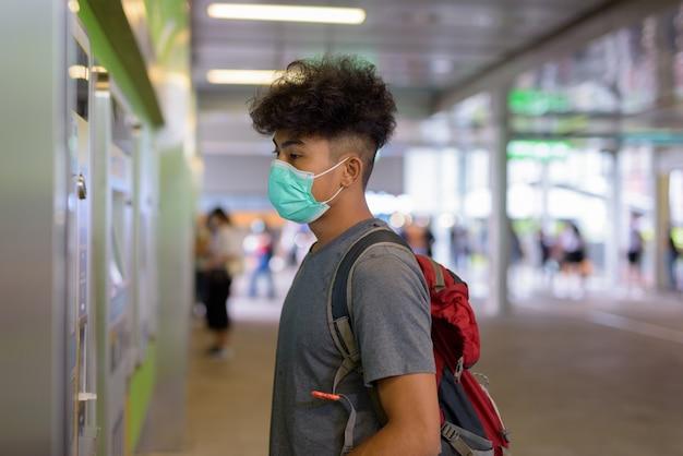 Retrato de jovem turista asiático como mochileiro com máscara para proteção contra surto de coronavírus na estação ferroviária do céu
