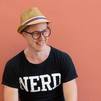 Retrato de jovem turista bonito como nerd contra fundo colorido ao ar livre