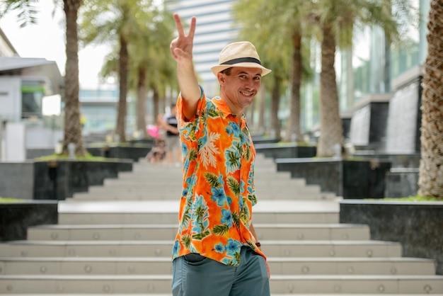 Retrato de jovem turista bonito do lado de fora de um shopping center na cidade