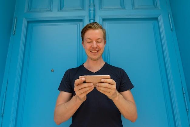 Retrato de jovem turista bonito em frente a uma porta azul