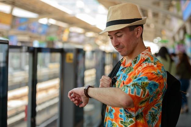 Retrato de jovem turista bonito na estação de trem do céu na cidade