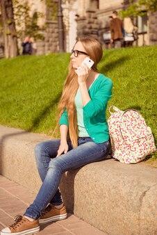 Retrato de jovem turista com mochila falando no telefone na cidade