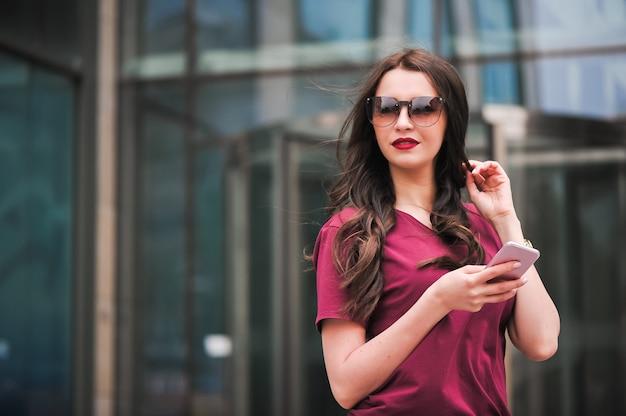 Retrato de jovem turista na cidade, usando telefone celular