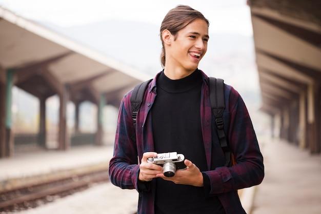 Retrato de jovem turista segurando uma câmera