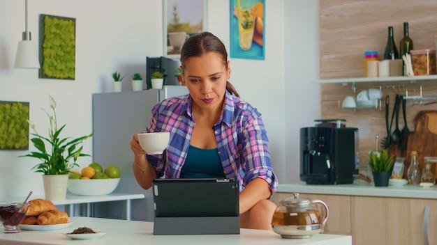 Retrato de jovem usando comprimido de manhã, sentado à mesa na cozinha, bebendo chá. trabalhar em casa usando um dispositivo com tecnologia de internet, digitação, no gadget durante o café da manhã.