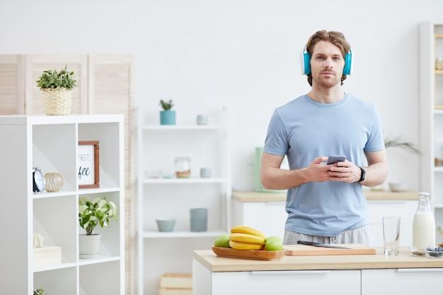 Retrato de jovem usando fones de ouvido e ouvindo música no telefone enquanto cozinha na cozinha