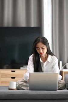 Retrato de jovem usando laptop, verificando e-mail ou trabalhando online enquanto está sentado no sofá em casa.