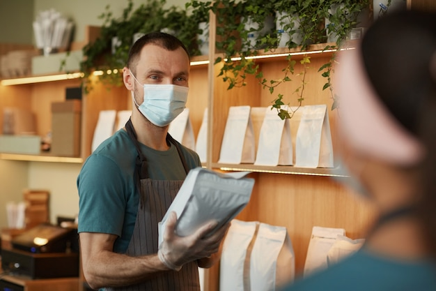Retrato de jovem usando máscara enquanto atendia um cliente no balcão de um café ou cafeteria, copie o espaço