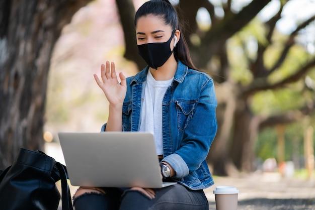 Retrato de jovem usando máscara facial em uma videochamada com laptop enquanto está sentado ao ar livre. conceito urbano. novo conceito de estilo de vida normal.