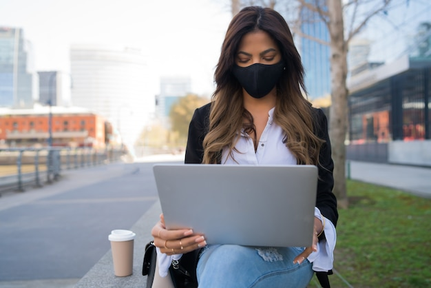 Retrato de jovem usando máscara protetora e usando seu laptop enquanto está sentado ao ar livre. conceito urbano. novo conceito de estilo de vida normal.
