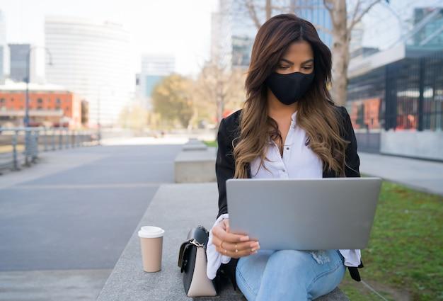Retrato de jovem usando máscara protetora e usando seu laptop enquanto está sentado ao ar livre. conceito urbano