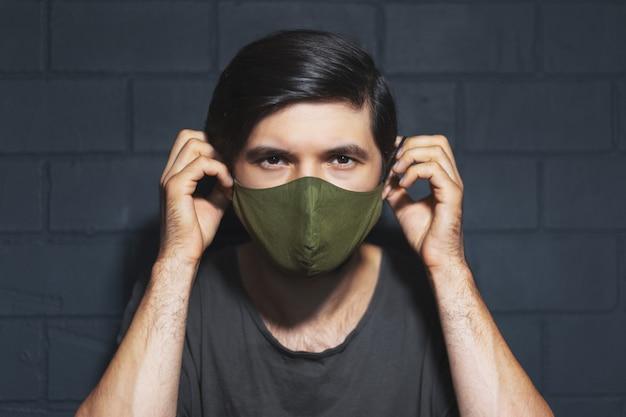 Retrato de jovem, usando máscara respiratória no rosto contra coronavírus e covid-19. plano de fundo da parede de tijolos pretos.