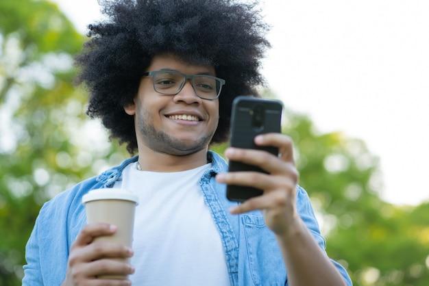 Retrato de jovem usando seu telefone celular em pé ao ar livre na rua
