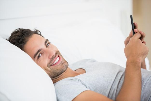 Retrato de jovem usando telefone celular na cama