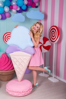 Retrato de jovem vestido rosa segurando sorvete grande e posando em fundo decorado. incrível garota gulosa, cercada por doces de brinquedo.