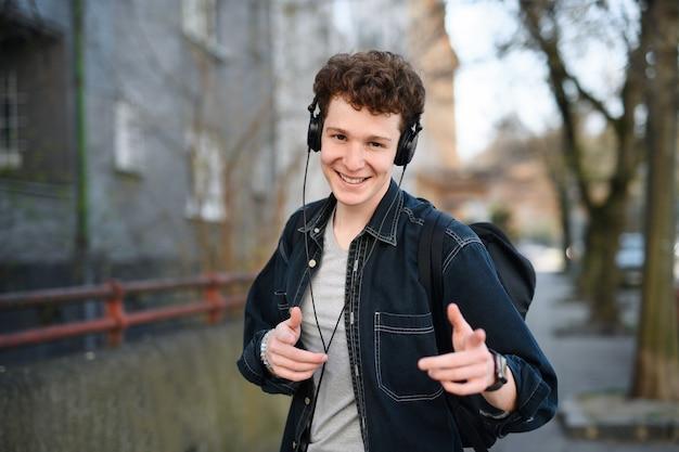 Retrato de jovem viajante com fones de ouvido, caminhando ao ar livre na cidade, olhando para a câmera.