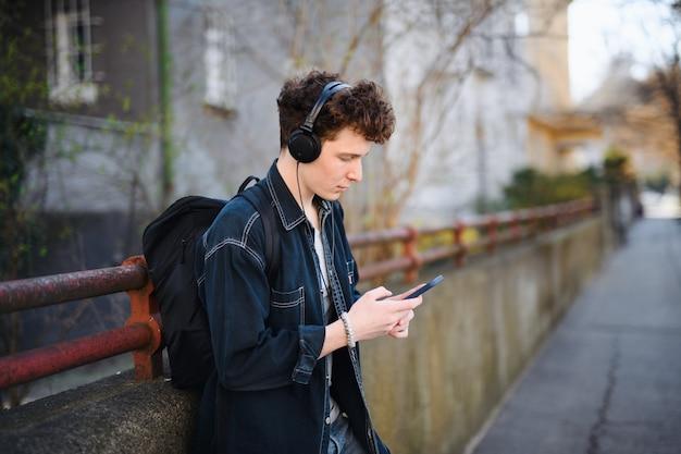 Retrato de jovem viajante com fones de ouvido em pé ao ar livre na cidade, usando o smartphone.