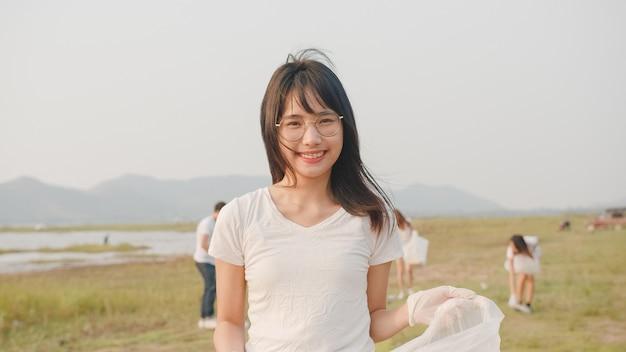 Retrato de jovem voluntária asiática ajuda a manter a natureza limpa, olhando para a frente e sorrindo com sacos de lixo brancos na praia