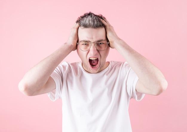 Retrato de jovem zangado com piercing na língua, usando óculos e camiseta branca