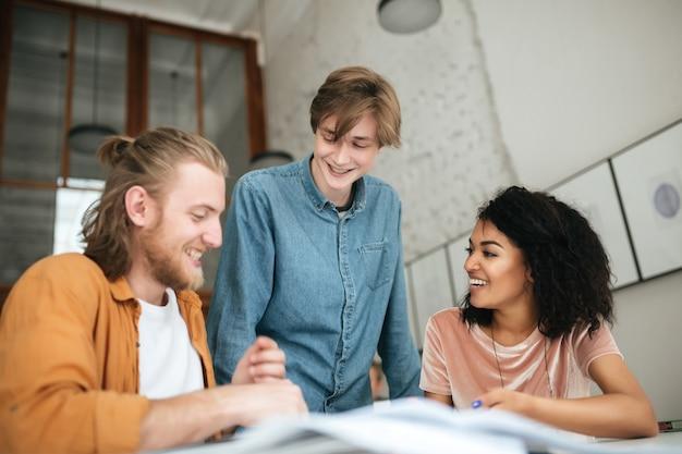 Retrato de jovens alegres discutindo algo no escritório