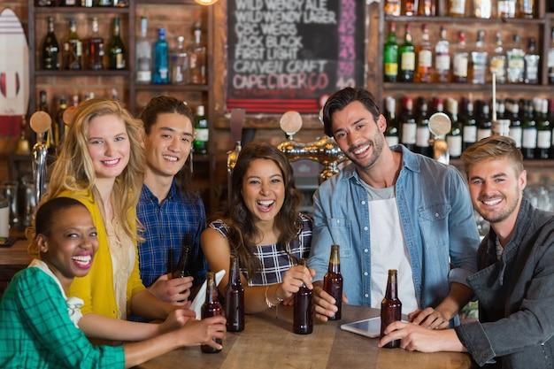 Retrato de jovens amigos alegres com garrafas de cerveja em um bar