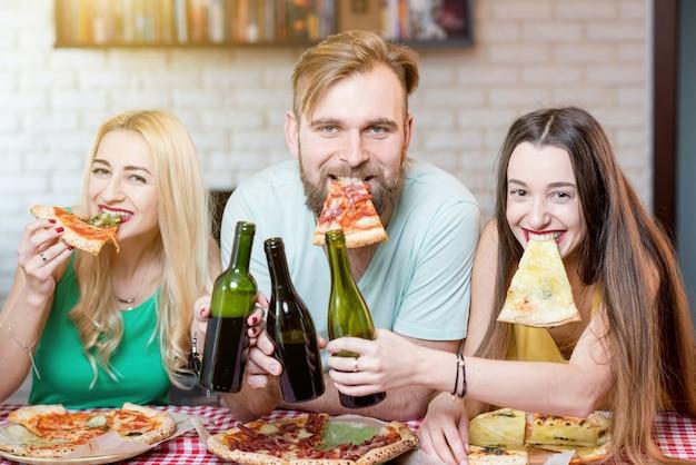 Retrato de jovens amigos engraçados vestidos casualmente com camisetas coloridas segurando uma fatia de pizza e cerveja em casa