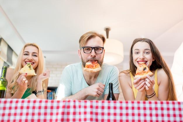 Retrato de jovens amigos engraçados vestidos casualmente com camisetas coloridas segurando uma fatia de pizza em casa
