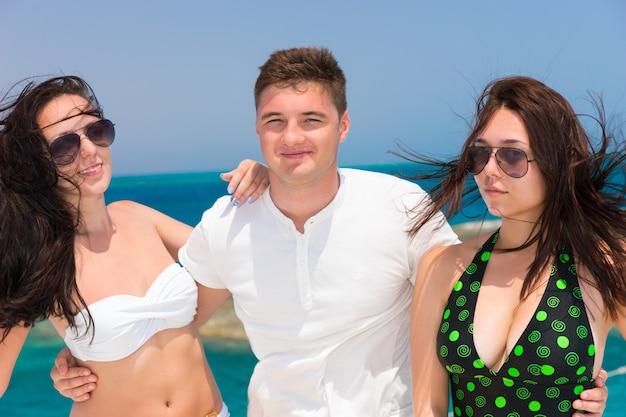 Retrato de jovens atraentes em pé no iate em um dia ensolarado de verão, brisa desenvolvendo cabelo, lindo mar no fundo