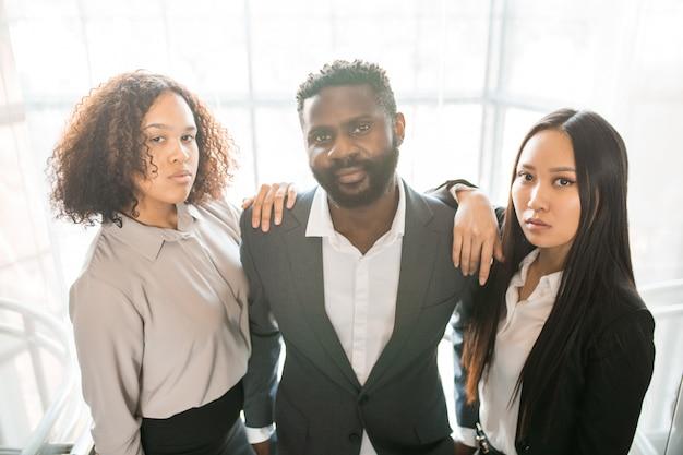 Retrato de jovens colegas multiétnicos sérios em trajes formais posando juntos no escritório