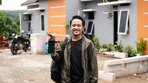 Retrato de jovens em frente de sua nova casa segurando um telefone verde