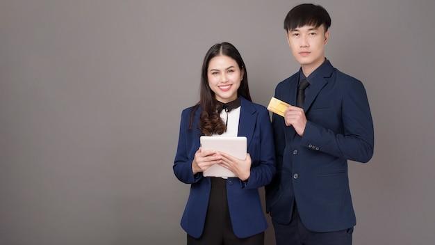 Retrato de jovens empresários asiáticos segurando o cartão de crédito no fundo cinza studio