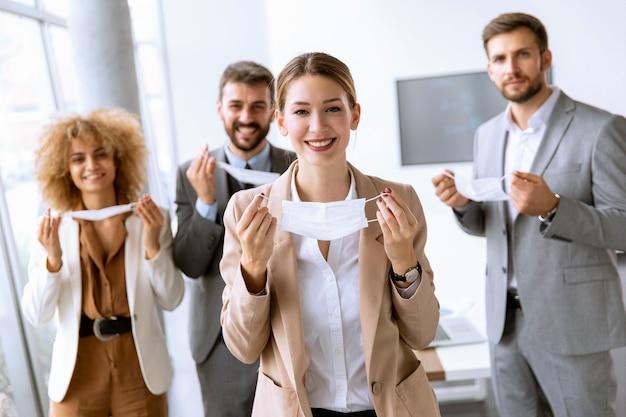 Retrato de jovens empresários tirando suas máscaras protetoras no escritório